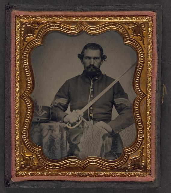 [Unidentified soldier in Union infantry sergeant's uniform holding a model 1840 non-comissioned officer's sword next to table with Company H, 6th Regiment Hardee hat on top]