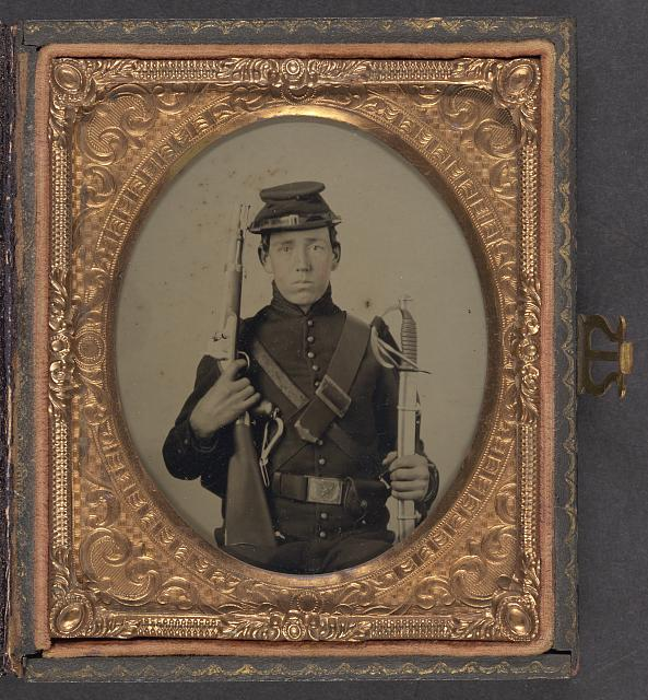 [Unidentified soldier in Union uniform holding a U.S. Model 1855 pistol-carbine with attached shoulder stock and a saber]