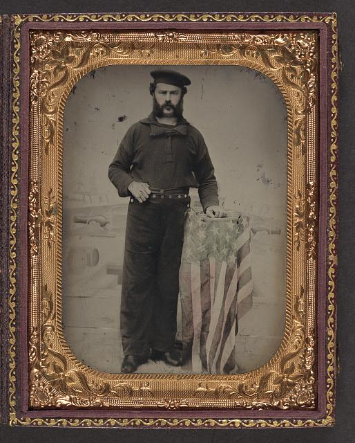 [Unidentified sailor in Union uniform at American flag-draped table in front of painted  backdrop showing Naval ship]