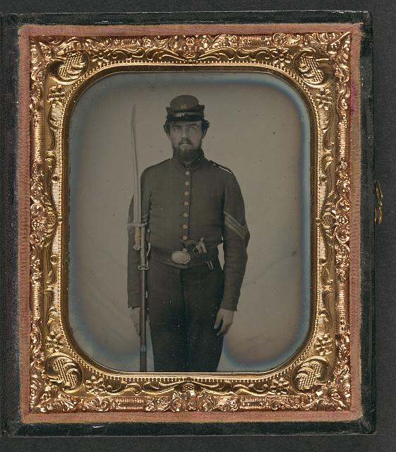 "[Unidentified soldier in Union sergeant's uniform and Company H forage cap with revolver, musket, and attached U.S. Model 1862 ""Zouave"" sword bayonet]"