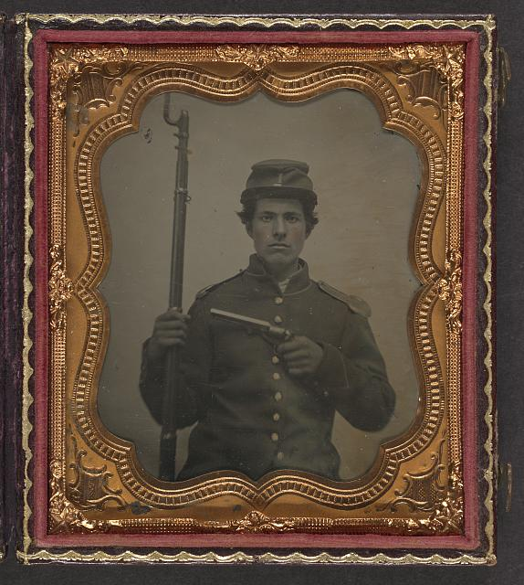 [Unidentified young soldier in Union uniform with shoulder scales and forage cap with Company I insignia holding revolver and bayoneted musket]
