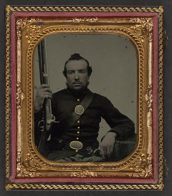 [Unidentified soldier in Union uniform with eagle breast plate holding a musket and bayonet in scabbard]