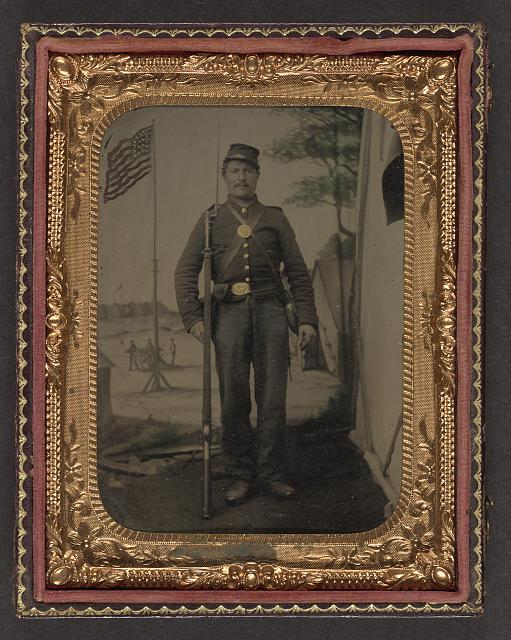 [Unidentified soldier in Union uniform with bayoneted musket, canteen, cartridge and cap boxes in front of painted backdrop showing military camp with American flag]