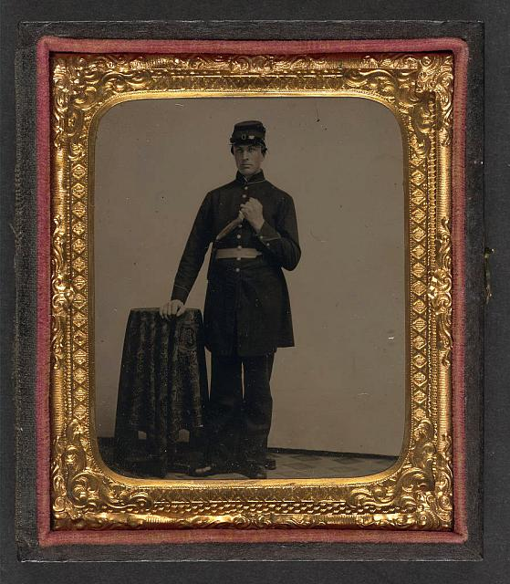 [Unidentified soldier in Union uniform with knife next to table]
