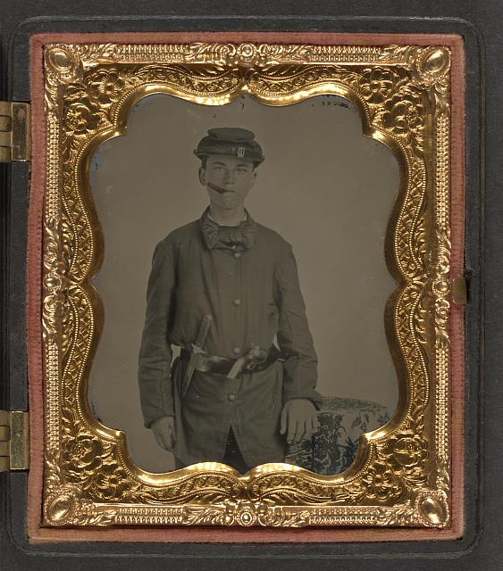 [Unidentified young soldier in Union uniform with revolver and knife in belt standing with a cigar in his mouth]