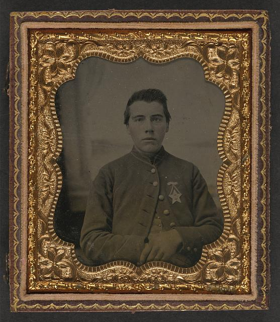 [Unidentified soldier in Union uniform with 28th Pennsylvania badge in front of painted backdrop showing window]