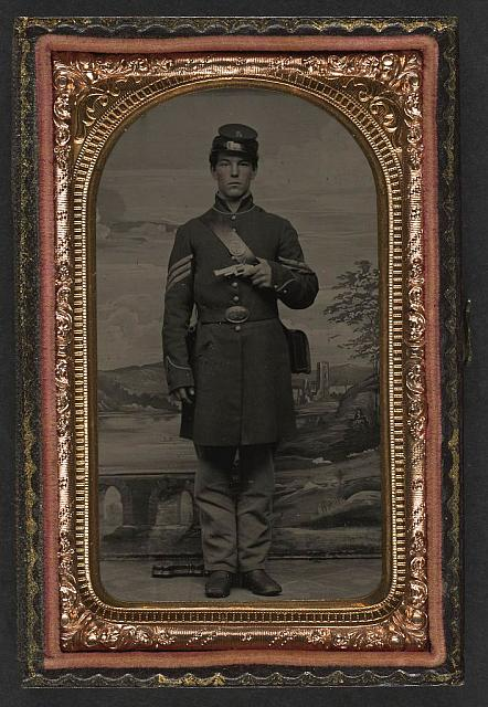 [Unidentified soldier in Union sergeant's uniform standing with revolver and cartridge box in front of painted backdrop showing countryside landscape]