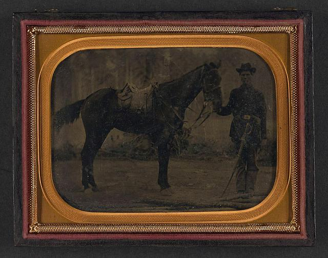 [Unidentified soldier in Union uniform with cavalry saber standing next to horse fitted with McClellan saddle]