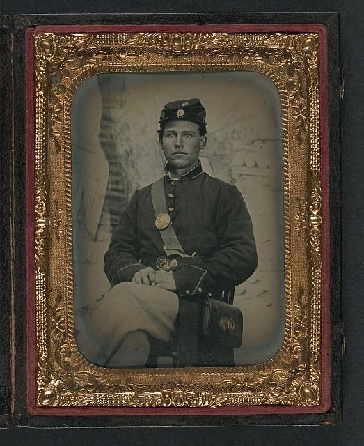 [Unidentified young soldier in Union uniform and Company D forage cap with handgun and cartridge box in front of painted backdrop showing military camp]