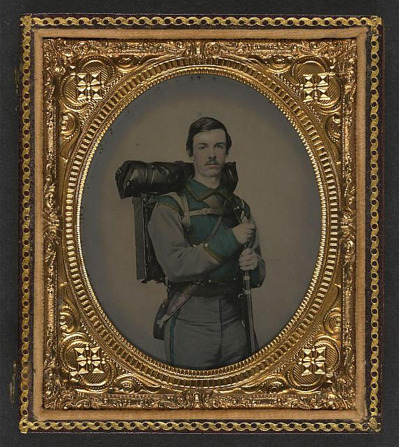 "[Unidentified soldier in Confederate uniform of Company E, ""Lynchburg Rifles,"" 11th Virginia Infantry Volunteers holding 1841 ""Mississippi"" rifle, Sheffield-type Bowie knife, canteen, box knapsack, blanket roll, and cartridge box]"