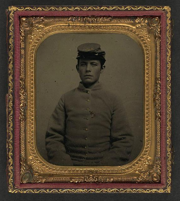 [Unidentified young soldier in Confederate shell jacket and artillery forage cap]