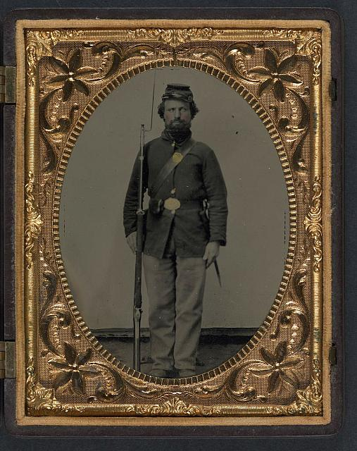 [Private George H. Bannister of Company H, 13th New Hampshire Infantry Regiment in sack coat and forage cap with holstered bayonet, cartridge pouch, and bayoneted musket]