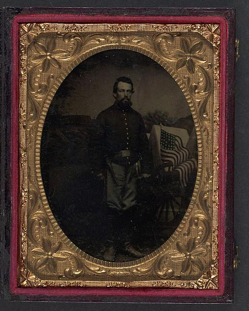 [Unidentified soldier in Union artillery shell jacket with revolver holster and sword in front of backdrop showing wagon and American flag]