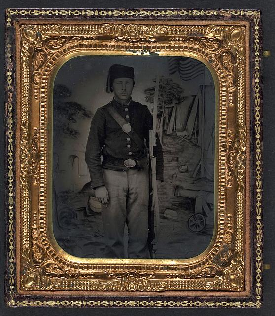"[Unidentified soldier in Union uniform, Zouave fez, and New York buckle with cap box, musket, and U.S. Model 1862 ""Zouave"" sword bayonet in front of painted backdrop showing military camp]"