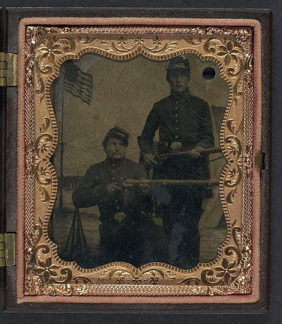[Brothers William and Philip J. Letsinger of Company D, 14th Indiana Regiment posing with rifles in front of Camp Michigan painted backdrop]