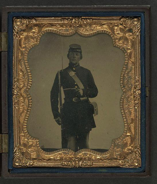 [Unidentified soldier in Union frock coat and forage cap with bayoneted musket and revolver]
