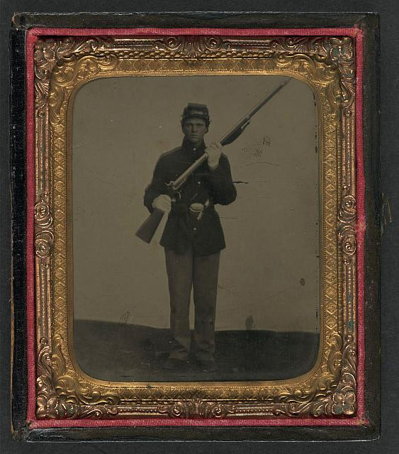 [Unidentified soldier in Union uniform and dress gloves with musket, revolver, and cap box]