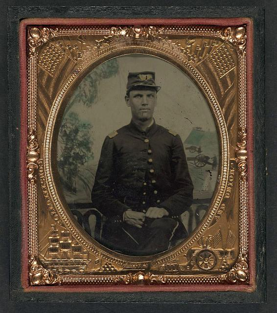 [Unidentified soldier in Union second lieutenant's uniform in front of painted backdrop showing battle scene]