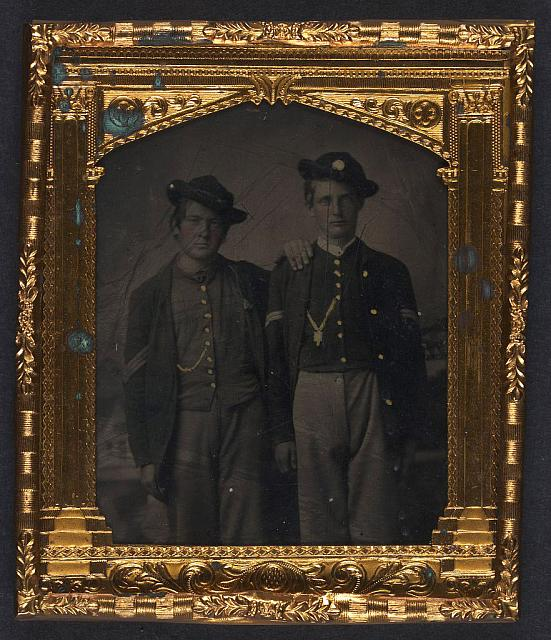 [Two unidentified soldiers in Union uniforms and slouch hats in front of painted backdrop]