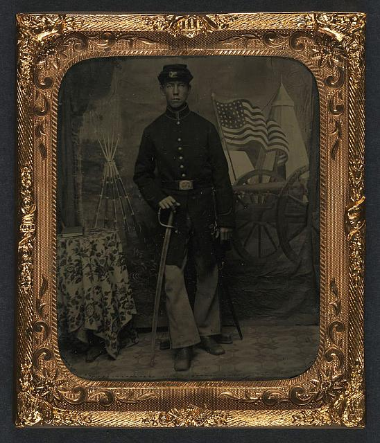 [Unidentified soldier in Union uniform with sword next to draped table with book in front of painted backdrop showing military camp]