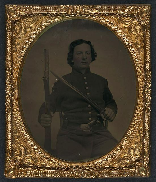 [Unidentified soldier in Union frock coat and SNY (State of New York) belt buckle with musket, sword bayonet, and revolver]