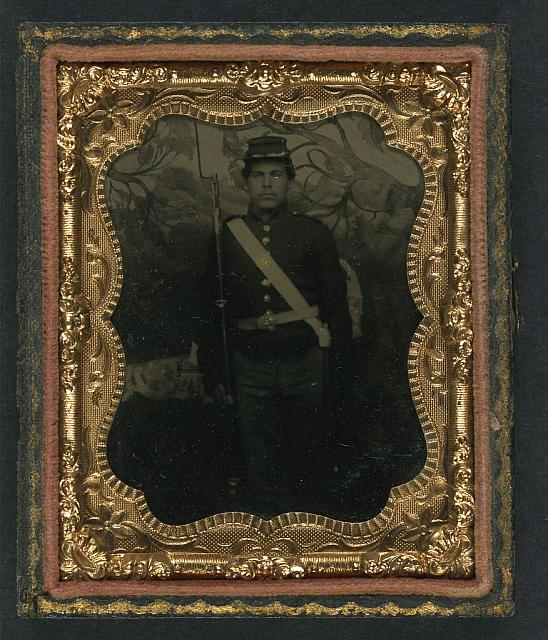 [Unidentified soldier in Union uniform with bayoneted musket in front of painted backdrop showing trees]