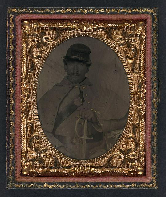 [Unidentified soldier in Union great coat and Company D forage hat with sword]