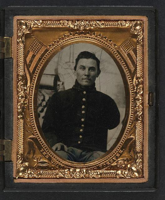 [Unidentified soldier with amputated arm in Union uniform in front of painted backdrop showing cannon and cannonballs]