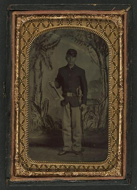 [Unidentified young soldier in Union uniform and infantry forage cap with sheathed musicans' sword and bugle in front of painted backdrop showing palm trees]