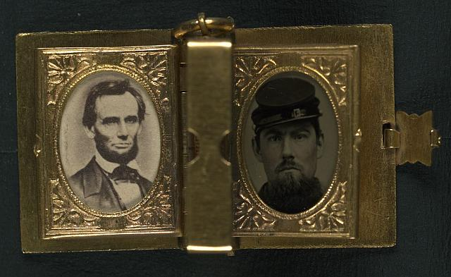 [Unidentified soldier in Union uniform and forage cap with portraits of Lincoln, Johnson, and an unidentified boy in a book-shaped locket with pages]