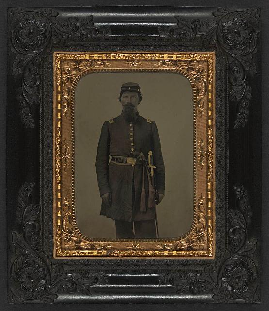 [Unidentified soldier in Union captain's frock coat and officer's sash with sheathed sword and revolver]