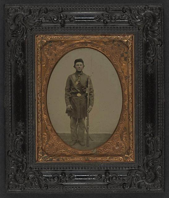[Unidentified soldier in Union frock coat and forage cap with bayonet scabbard and bayoneted musket]