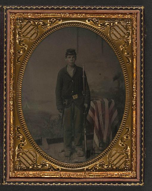 [Unidentified young soldier in Union sack coat and forage cap with musket and sheathed bayonet in front of backdrop showing landscape]