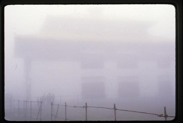 [People standing in front of building in mist, Sikkim]