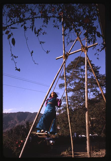 [A young girl swinging on a handcrafted swing, Sikkim]