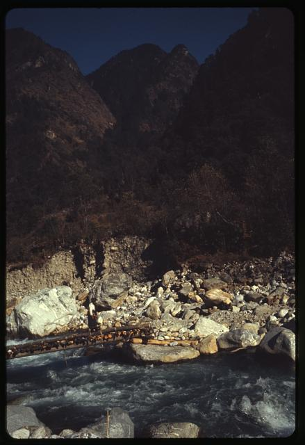 [Person crossing river on wooden bridge, Sikkim]
