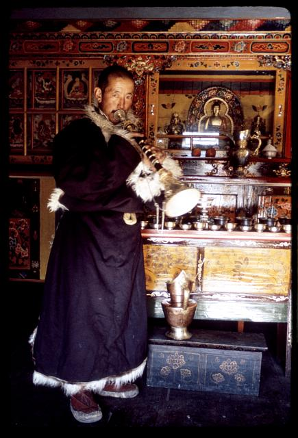 [Rinchen Namgyal Lachungpa blowing a gyaling in front of altar in his home, Lachung, Sikkim]