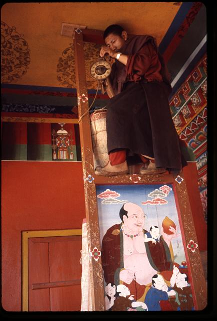 [Monk fixing clock above painting, Sikkim]