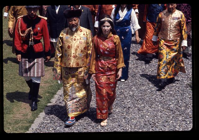 [Palden Thondup Namgyal, King of Sikkim, and Hope Cooke, Queen of Sikkim, in brocaded dress, walking to the palace temple during the King's birthday celebration, Gangtok, Sikkim]