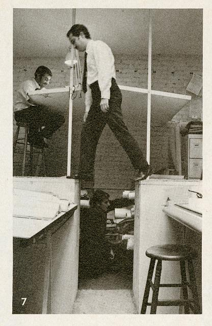 [Paul Rudolph's architectural office in Manhattan. Man stepping across file cabinet tops among elevated drafting stations]