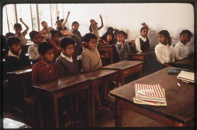 [Schoolchildren raising hands in classroom, Sikkim]