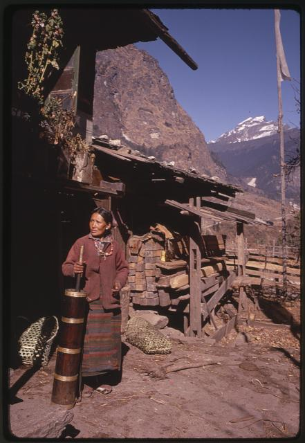 [Woman, with churn, standing by structure, prayer flag in background, Lachung, Sikkim]