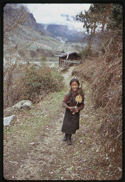 [Girl from the Jorbu family, full-length portrait, standing in road, holding religious article?, Lachung, Sikkim]