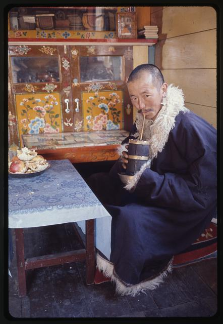 [Rinchen Namgyal Lachungpa, full-length portrait, seated, drinking millet beer at his home, Lachung, Sikkim]