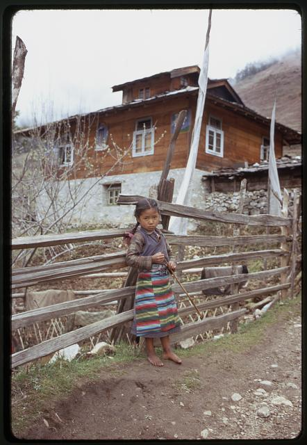 [Girl from the Jorbu family, full-length portrait, standing in road next to fence, building with prayer flags in background, Lachung, Sikkim]