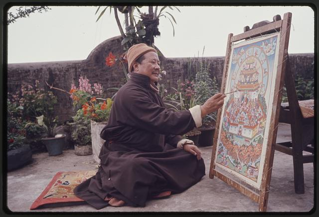 [Man, seated on ground outdoors, working on a religious painting, Sikkim]
