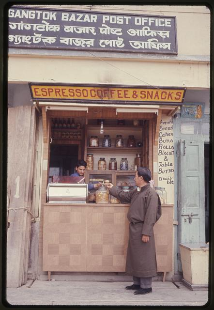 [Man buying items from coffee and snack vendor in shop along a street, Gangtok, Sikkim]