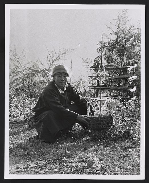 [Man squatting outdoors holding a basket with a religious offering (?), Sikkim]