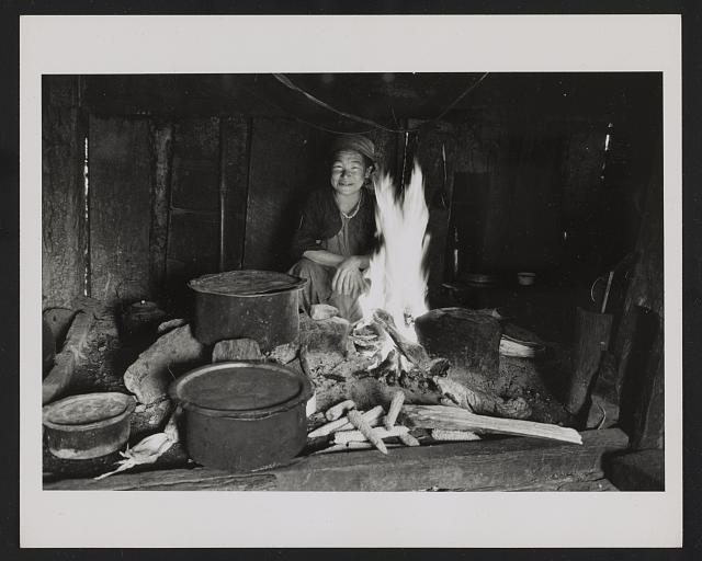 [Kiranti woman cooking at the hearth in her house, Sikkim]