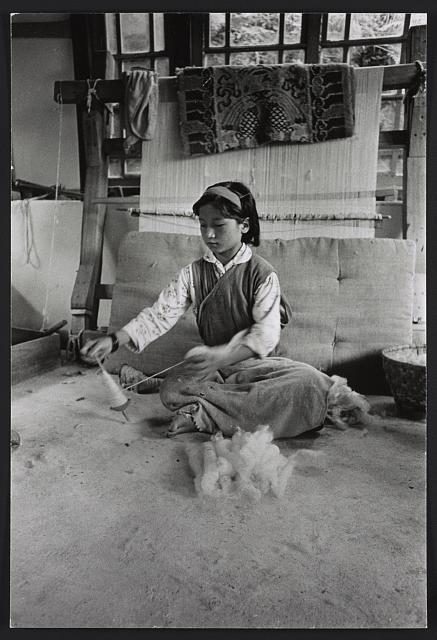 [Girl sitting in front of loom, spinning fiber with a hand spindle, Sikkim]